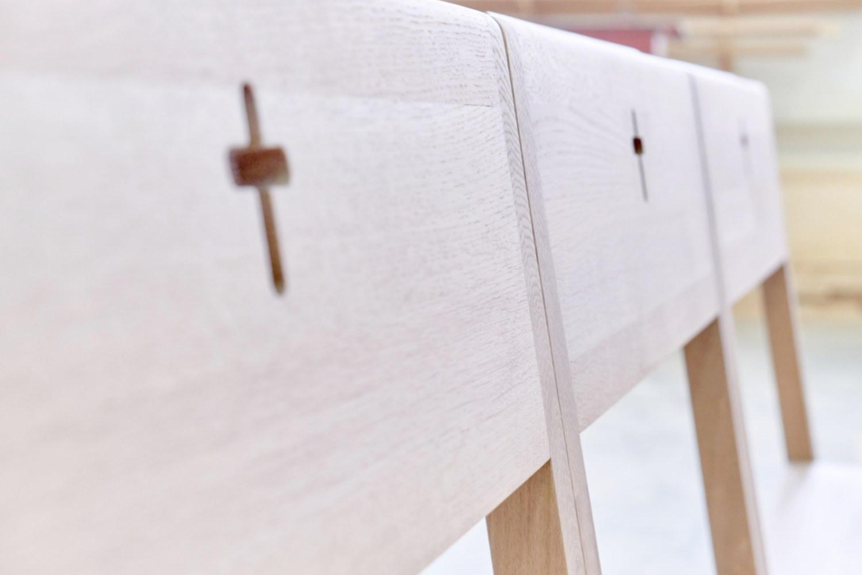 KIRCHENSTÜHLE aus Holz mit Kreuz in der Kirche.